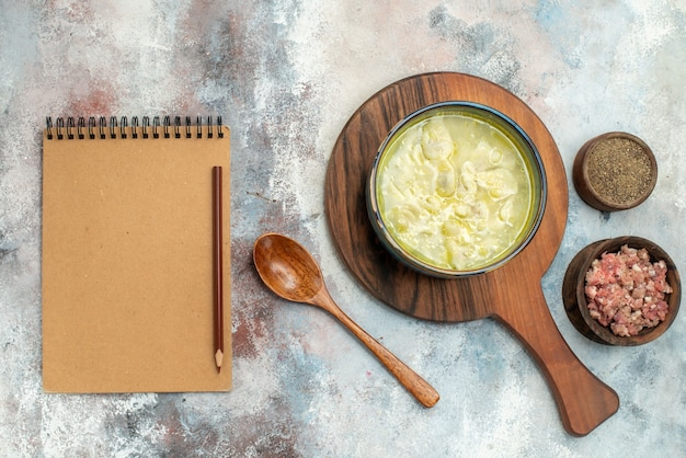 Vista dall'alto zuppa di gnocchi di dushbara sul tagliere ciotole con carne e pepe cucchiaio di legno un taccuino sulla superficie nuda