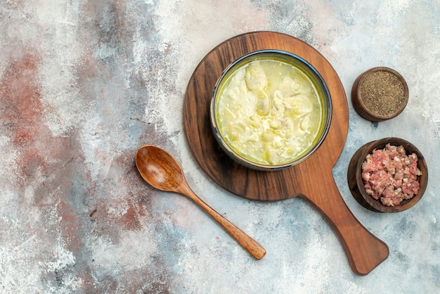Top view dushbara dumplings soup on cutting board bowls with meat and pepper wooden spoon on nude surface free place