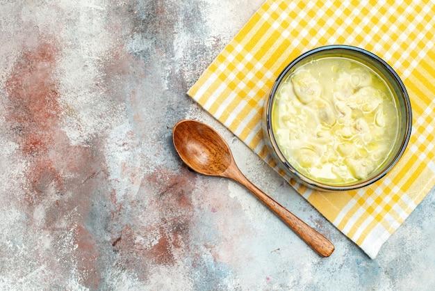 上面図黄色と白の市松模様のキッチンタオルのボウルにスープのdushbara餃子ヌード表面の空きスペースに木のスプーン
