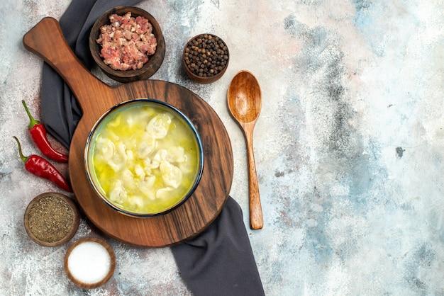 まな板の上のビューdushbara黒いテーブルクロスボウルと肉の異なるスパイス木のスプーンヌード表面のコピースペース