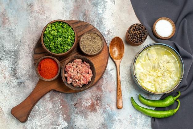 Vista dall'alto dushbara un cucchiaio di legno asciugamano da cucina nero ciotole di peperoncino con pepe nero ciotole di sale con verdure di carne spezie diverse sul tagliere sulla superficie nuda