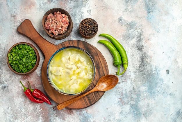 Vista dall'alto dushbara un cucchiaio di legno sul tagliere ciotole con verdure di carne pepe nero peperoncini piccanti sulla superficie nuda spazio libero