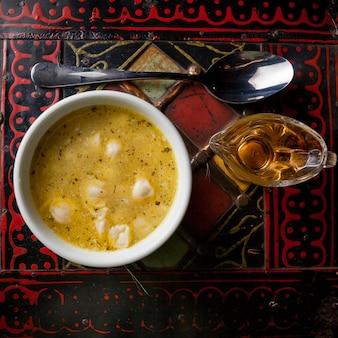 Dushpara vista dall'alto con cucchiaio e aceto nel piatto bianco