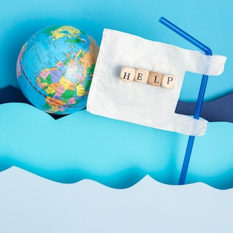 Top view of earth globe with plastic straw and paper ocean waves