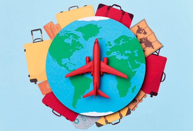 Top view earth surrounded by luggage and airplane