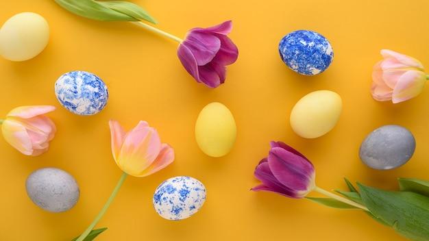 Вид сверху пасхальный фон фиолетовых и розовых тюльпанов, пастельных желтых, синих яиц на желтом фоне