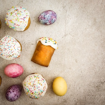 Top view of easter cakes and colored eggs on textured background