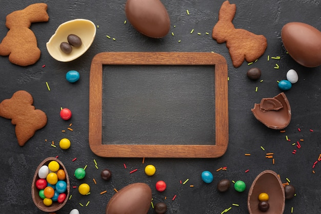 Top view of easter chocolate eggs with bunny shaped cookies and blackboard