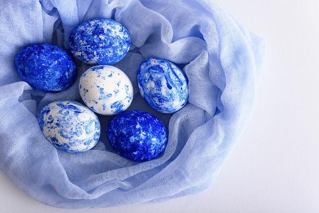 Вид сверху пасхальные классические синие яйца в мягкой синей салфетке на белом фоне