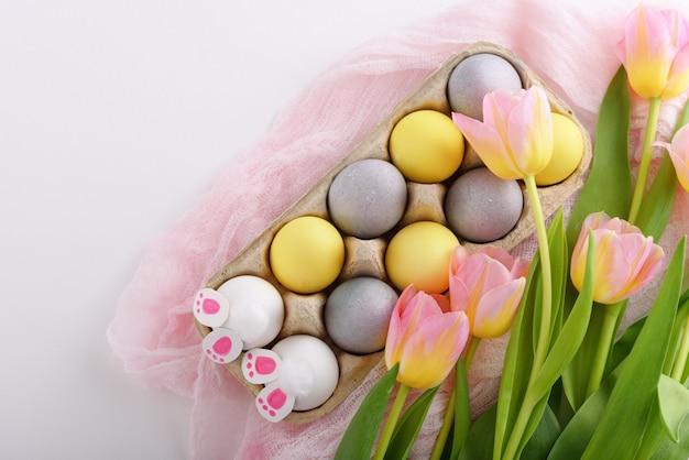 上面図白い背景の上の段ボール箱の卵、チューリップ、ウサギの足のイースター構成