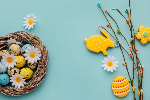 Top view of easter eggs in basket with chamomile flowers