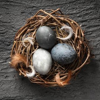 Vista dall'alto di uova di pasqua nel nido di uccelli fatti di ramoscelli con piume