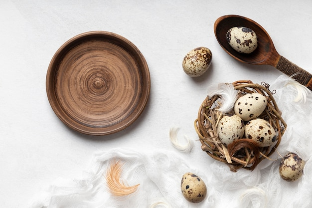 Top view of easter eggs in bird nest with feathers and empty plate