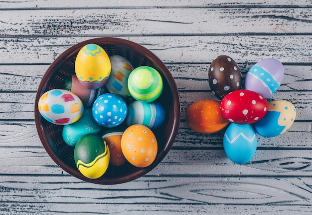Top view easter eggs in bowl on light wooden background.