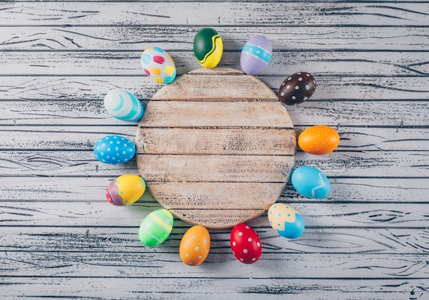 Top view easter eggs in bowl with circular wood on light wooden background.
