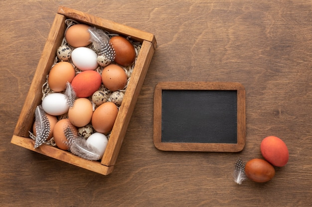 Top view of easter eggs in a box with feathers and blackboard