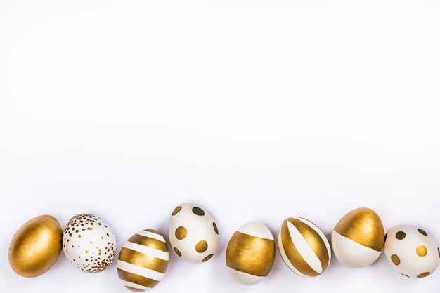 Top view of easter eggs colored with golden paint in different patterns.