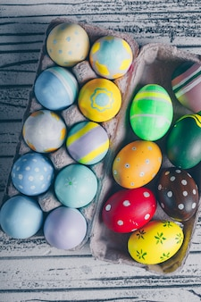 Top view easter eggs in egg carton on light wooden background.