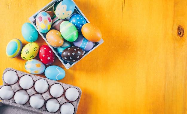 木製の背景が黄色の木製の箱と卵のカートンで平面図イースターエッグ。