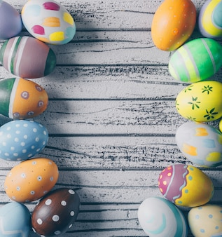 Top view easter eggs on light wooden background. vertical space for text