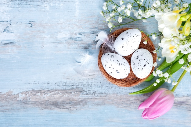 Top view of easter eggs in a nest. spring flowers and feathers over blue rustic wooden table.