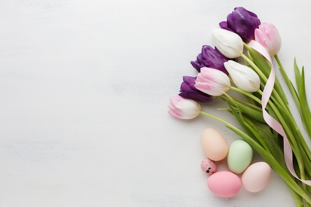 Top view of easter eggs with colorful tulips and copy space