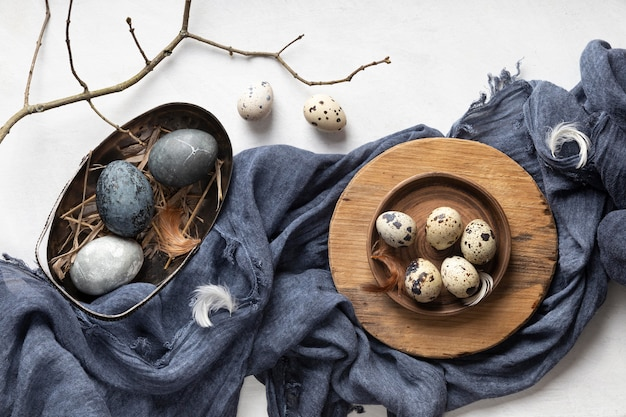 Vista dall'alto di uova di pasqua con ramoscello e tessuto