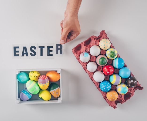 Top view easter eggs in wooden box and egg carton with easter text on white background.