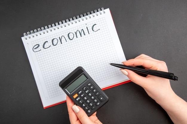 Vista dall'alto economica scritta sul calcolatore del blocco note a spirale e penna in mani femminili su oscurità