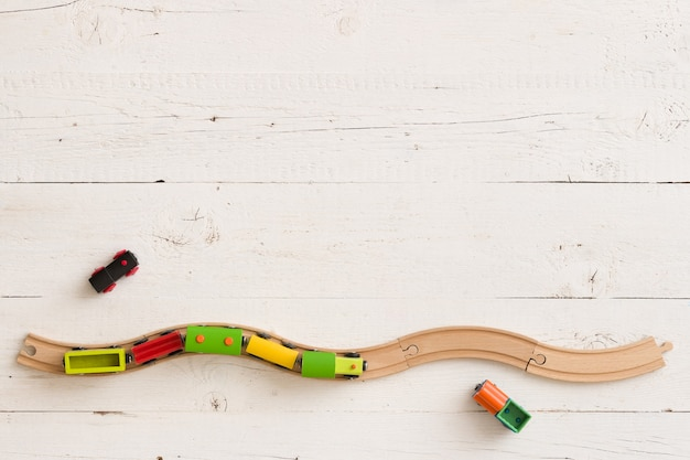 Top view of educational toy wooden train with rails on white wooden background
