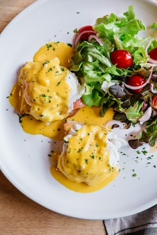 Top view of egg benedict served with salad in white plate.