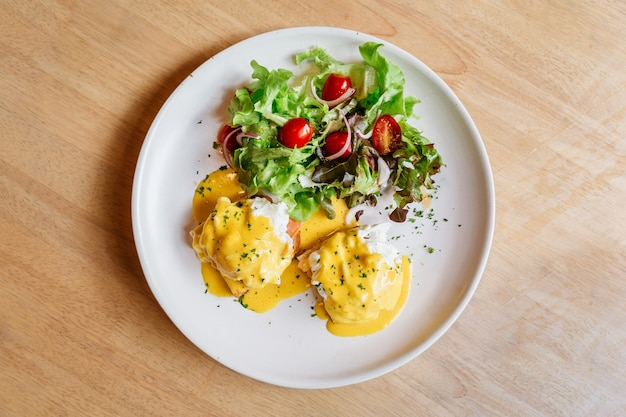 Top view of egg benedict served with salad.