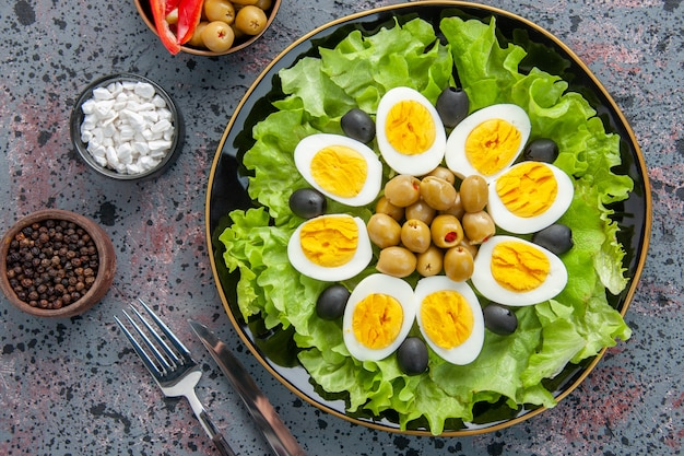 Top view egg salad consists of green salad and olives on light background