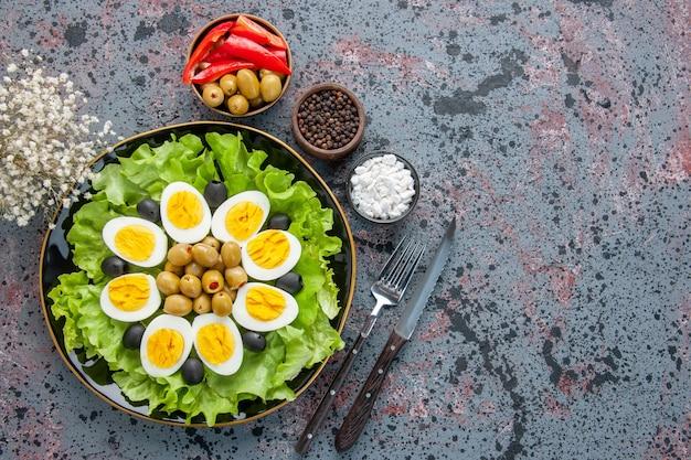 トップビューのエッグサラダは、明るい背景にグリーンサラダとオリーブで構成されています