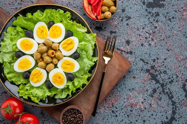 밝은 배경에 토마토와 상위 뷰 계란 샐러드 그린 샐러드와 올리브