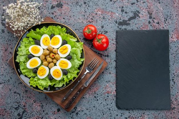 Vista dall'alto insalata di uova insalata verde e olive con pomodori rossi su sfondo chiaro