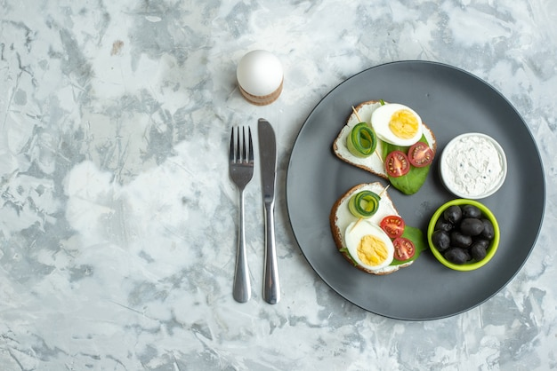 トップビュープレートの内側にナイフとフォークが付いた卵サンドイッチ白い背景サンドイッチダイエット健康ハンバーガーパン食事ランチフードトースト空きスペース