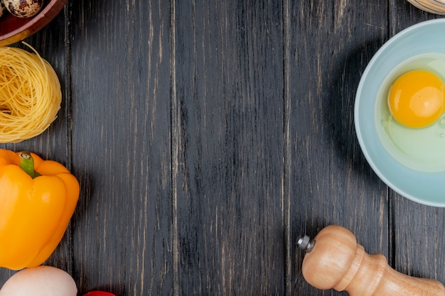 Top view of egg yolk and white on a bowl with an orange bell pepper on a wooden background with copy space