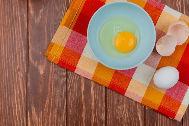Top view of egg yolk and white on a white bowl with cracked egg shells on checked cloth on a wooden background with copy space