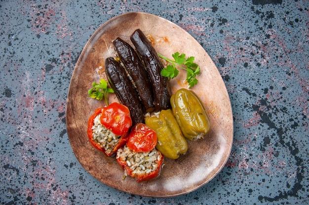 Вид сверху долма из баклажанов с вареными помидорами и болгарским перцем, начиненная мясным фаршем, внутри тарелки, пищевой краситель для ужина