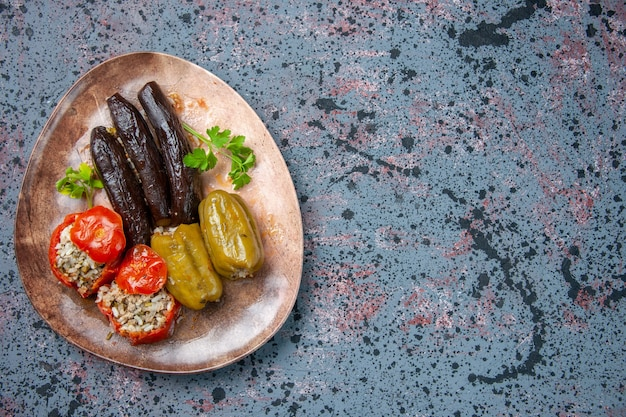 Вид сверху долма из баклажанов с вареными помидорами и болгарским перцем, начиненная мясным фаршем, внутри тарелки, блюдо ужин пищевой краситель