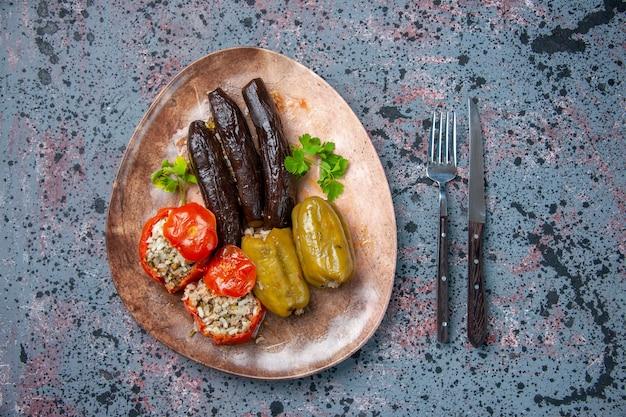 Вид сверху долма из баклажанов с вареными помидорами и болгарским перцем, начиненная мясным фаршем, внутри тарелки, блюдо, цвет обеда