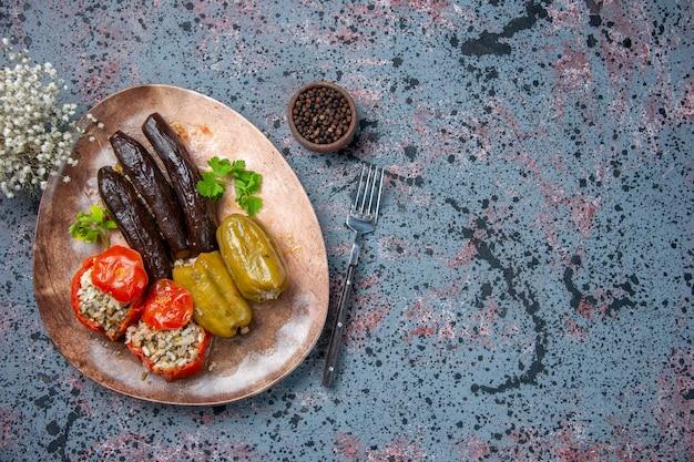 Вид сверху долма из баклажанов с вареными помидорами и болгарским перцем, начиненная мясным фаршем внутри тарелки, обеденный обед с пищевым красителем
