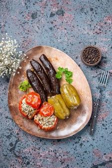 Вид сверху долма из баклажанов с вареными помидорами и болгарским перцем, начиненная мясным фаршем внутри тарелки, блюдо обеденное блюдо