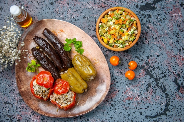 Top view eggplant dolma with cooked tomatoes and bell-peppers filled with ground meat inside plate, dish color dinner food meal