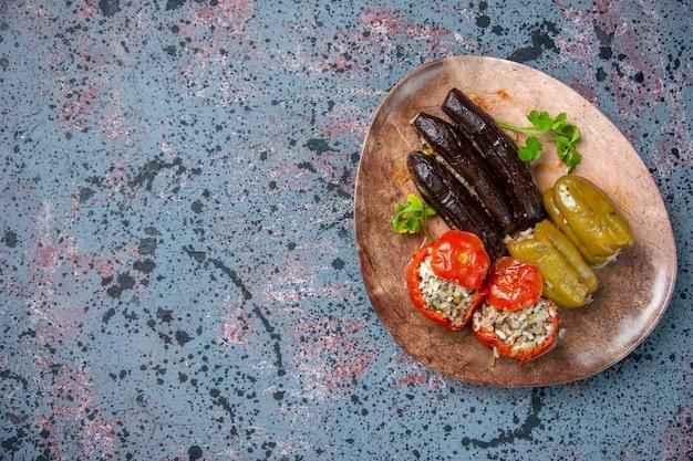 Vista dall'alto dolma di melanzane con pomodori cotti e peperoni ripieni di carne macinata all'interno del piatto, cena a colori