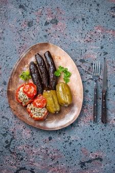 Vista dall'alto dolma di melanzane con pomodori cotti e peperoni ripieni di carne macinata all'interno del piatto, colore del pasto del piatto di cibo