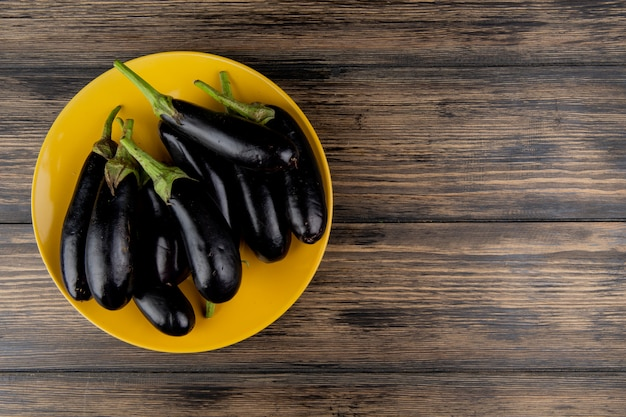 Top view of eggplants in plate on left side and wooden background with copy space