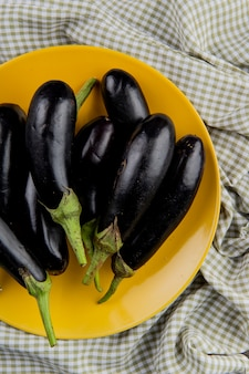 Top view of eggplants in plate on plaid cloth background