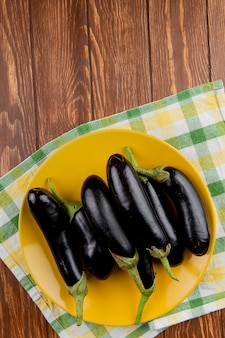 Top view of eggplants in plate on plaid cloth and wooden background with copy space